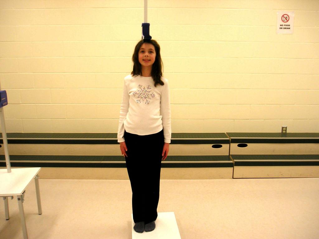 Девочка измеряет рост стоя.